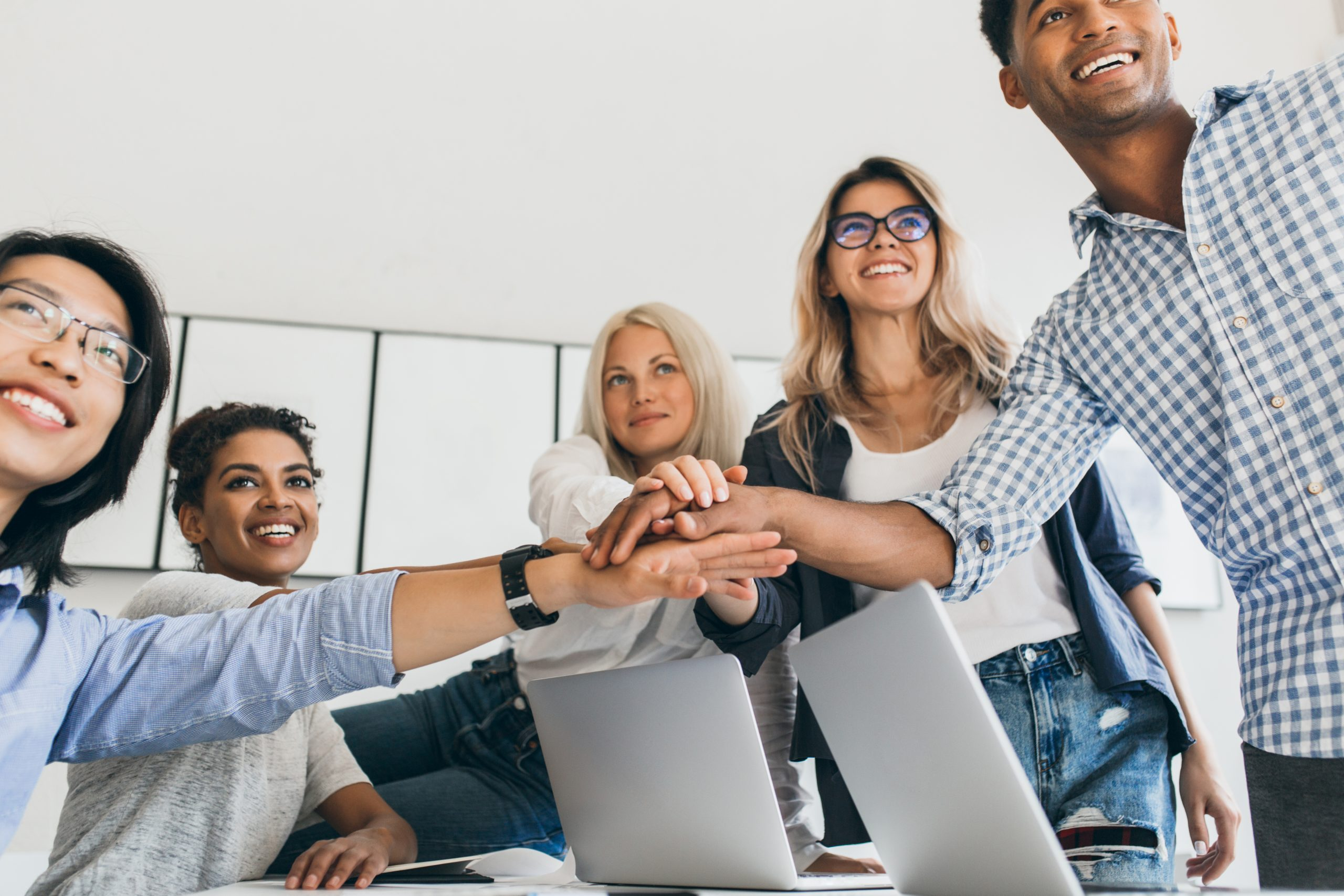 Asian businessman in leather wristwatch holding hands with partners and smiling. Indoor portrait of team of office workers having fun before big project..