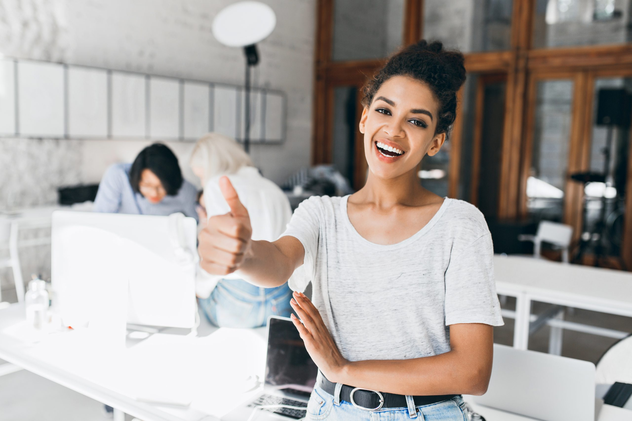 Joyful african female student with short hairstyle holding thumb up after passing exams. Portrait of happy black girl in gray t-shirt having fun in office while her colleagues working on project..